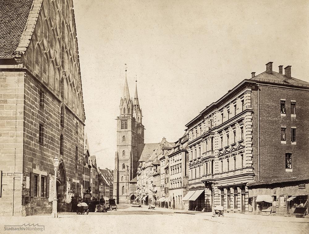Schräg gegenüber der Mauthalle befand sich in der nordwestlichen Erdgeschosshälfte – erkennbar an den beiden ausgefahrenen Markisen – des Hauses Königstraße 41 für rund zwei Jahrzehnte das erste Ladenlokal der Firma S. Guttmann. Foto, um 1880. (Stadtarchiv Nürnberg A 60/I Nr. 269)